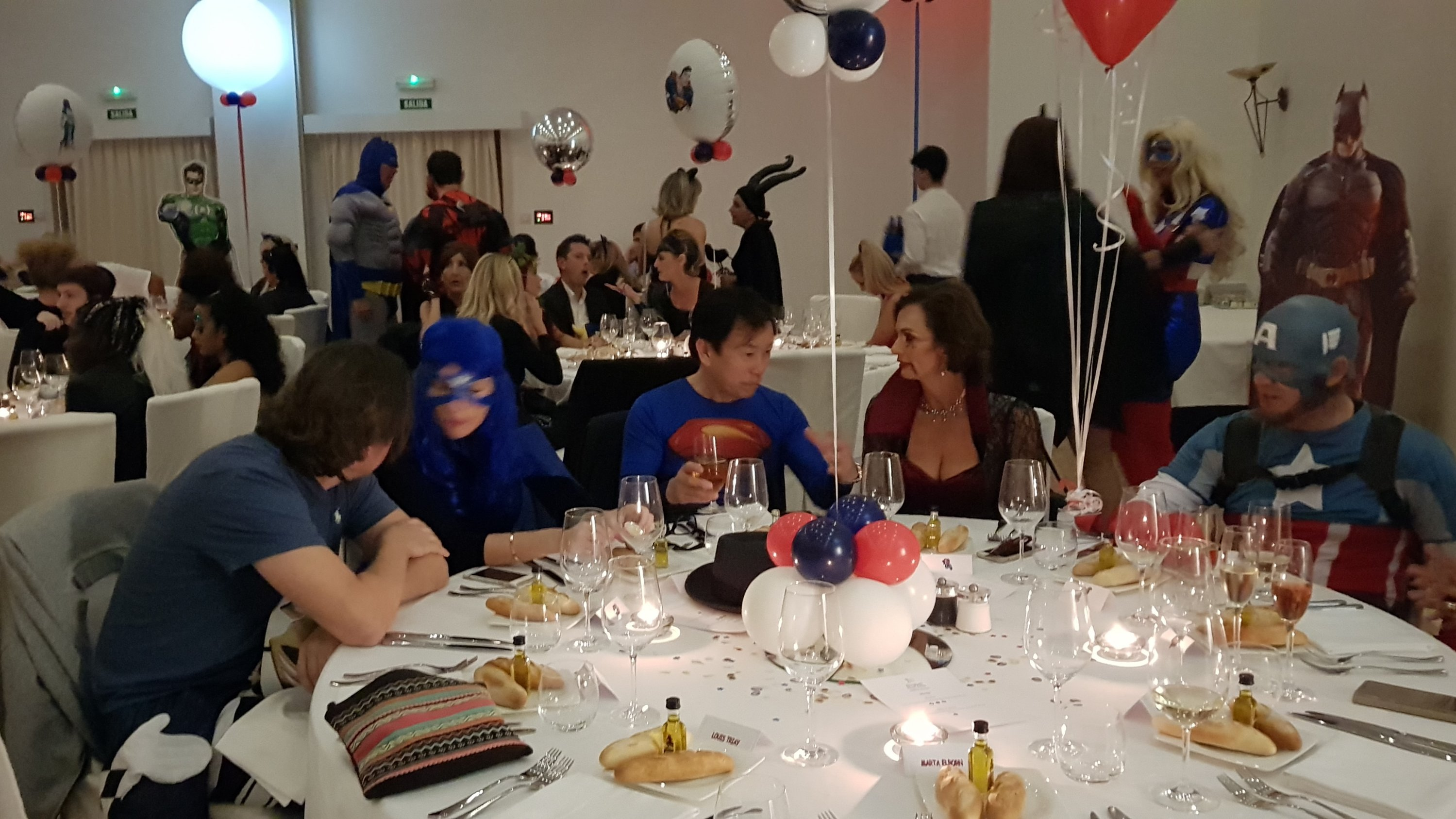 Birthday party guests enjoying dinner party dressed as Superheroes and supervillains