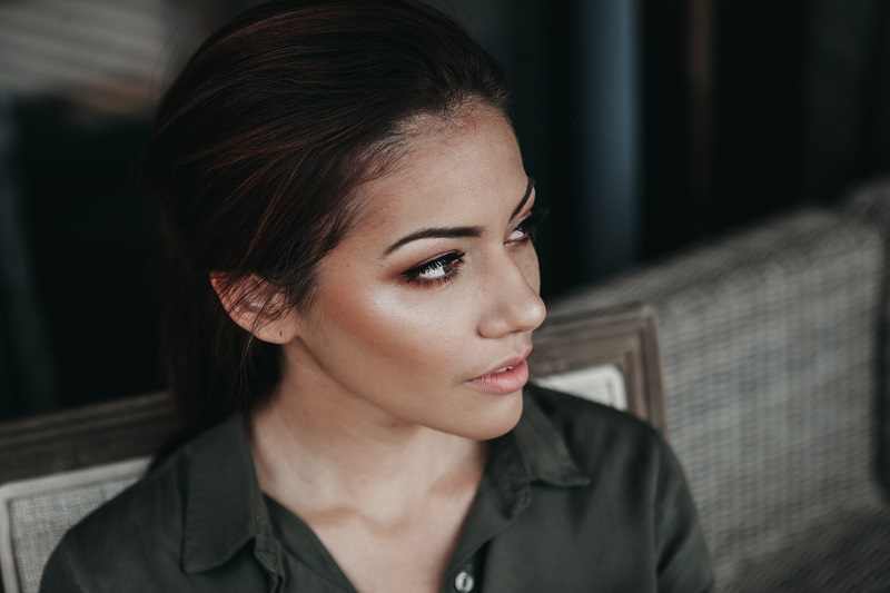 A woman with dark hair and dewy makeup.